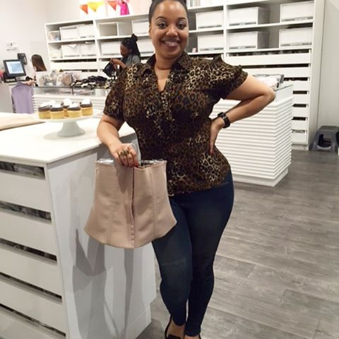 A curvy black lay holding a squeem package at a store