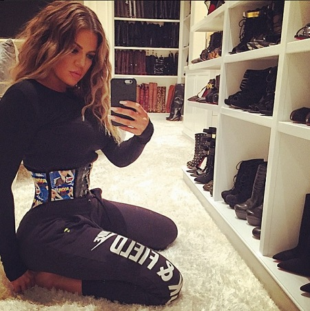 Khloe Kardashian wearing a multi colored waist trainer cincher and taking a selfie in her closet while on her knees