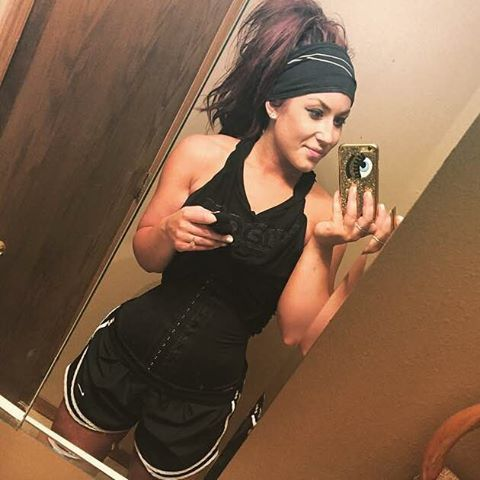 girl taking a selfie with a black waist trainer in her gym clothes and a sweat band on head
